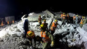 Les soldats de sécurité de patrie évacuent les personnes blessées par tsunami d'attaque de fusée de tremblement de terre Image libre de droits