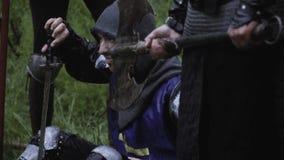Les soldats m?di?vaux dans l'armure en m?tal se reposent dans le camp de for?t, sous la pluie banque de vidéos