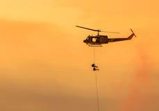 Les soldats s'élèvent vers le bas de l'hélicoptère dans la mission militaire photo libre de droits