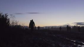 Les soldats sont sur le champ boueux au coucher du soleil Nuit militaire banque de vidéos