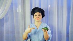 Les sourires femelles d'un chef, tient un avocat dans sa main et des points sur elle banque de vidéos