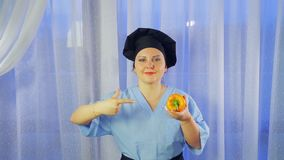 Les sourires femelles d'un cuisinier, tient un poivre jaune dans sa main et des points sur elle banque de vidéos