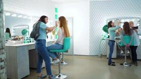 Les spécialistes en maquillage et en coupe de cheveux préparent les filles modèles pour un défilé de mode banque de vidéos