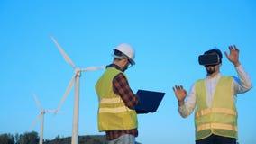 Les spécialistes masculins se tiennent près des moulins à vent et travaillent avec la réalité virtuelle banque de vidéos