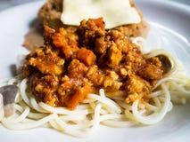 Les spaghetti avec le poulet frit ont complété avec du fromage, placé sur un plat blanc Image libre de droits