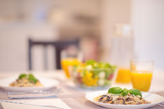 Les spaghetti frais avec la sauce aux champignons et le basilic crémeux poussent des feuilles Photos stock