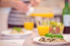 Les spaghetti frais avec la sauce aux champignons et le basilic crémeux poussent des feuilles photographie stock libre de droits