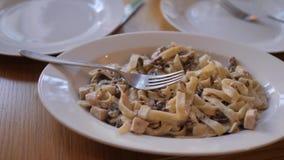 Les spaghetti italiens avec de la sauce, les champignons et le basilic poussent des feuilles vidéo animée lente Tagliatelles de p banque de vidéos
