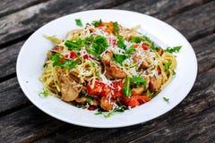 Les spaghetti italiens de blanc de poulet avec le poivron rouge, le parmesan et la fusée sauvage vivent sur la vieille table en b Image stock