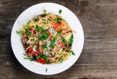 Les spaghetti italiens de blanc de poulet avec le poivron rouge, le parmesan et la fusée sauvage vivent sur la vieille table en b Photo stock