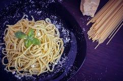 Les spaghetti italiens de pâtes avec de la sauce et le basilic faits maison à pesto poussent des feuilles photo libre de droits