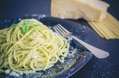 Les spaghetti italiens de pâtes avec de la sauce et le basilic faits maison à pesto poussent des feuilles image libre de droits