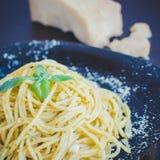Les spaghetti italiens de pâtes avec de la sauce et le basilic faits maison à pesto poussent des feuilles photographie stock