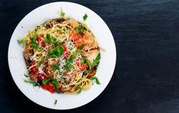 Les spaghetti italiens de pâtes de blanc de poulet avec le poivron rouge, le parmesan et la fusée sauvage vivent sur la vieille t Image libre de droits