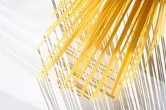 Les spaghetti se tiennent verticalement sous la lumière du soleil sur un blanc Photo stock