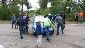 Les spectateurs aident à retourner la voiture de rassemblement sur le toit Accident avec la voiture de rassemblement clips vidéos