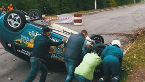 Les spectateurs aident à retourner la voiture de rassemblement sur le toit Accident avec la voiture de rassemblement banque de vidéos