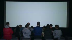 Les spectateurs applaudissent le film qui a fini Assistance laissant des applaudissements de cinéma banque de vidéos