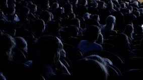 Les spectateurs observent l'exposition ou la regardent dans le théâtre Vidéo du dos Enfants et adultes semblables Longueur d'agra clips vidéos