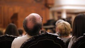 Les spectateurs observent la représentation théâtrale - homme et femme chauves banque de vidéos