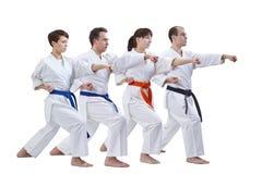 Les sportifs avec différentes couleurs des ceintures ont battu le bras de poinçon sur un fond blanc Images stock