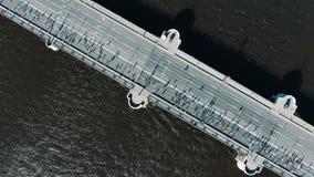 Les sportifs courent le marathon le long du pont en route avec l'inscription blanche banque de vidéos