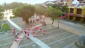 Les sportifs dans des robes rouges et blanches s'exercent pour la représentation clips vidéos