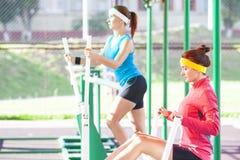 Les sportives dans le bon ajustement utilisant l'équipement professionnel ayant des bras et des muscles de jambes s'exerce photographie stock