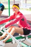 Les sportives dans le bon ajustement utilisant l'équipement professionnel ayant des bras et des muscles de jambes s'exerce images libres de droits