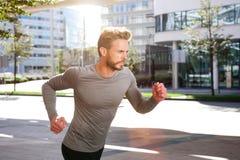 Les sports actifs équipent l'extérieur courant dans la ville image stock