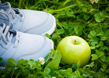 Les sports chausse les espadrilles et la pomme sur l'herbe verte fraîche Foyer sélectif Photos libres de droits