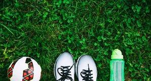 Les sports chausse les espadrilles, la boule et la bouteille de l'eau sur une herbe verte fraîche Photos libres de droits