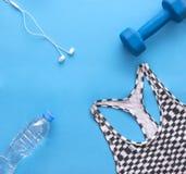 Les sports complètent, haltère bleue, les écouteurs, bouteille d'eau sur le dos de bleu Image stock