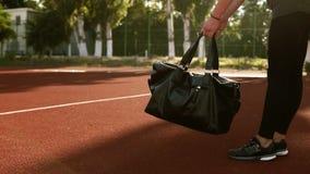Les sports de transport de jeune jolie femme de forme physique mettent en sac tout en marchant par le stade d'extérieur Aucun vis clips vidéos