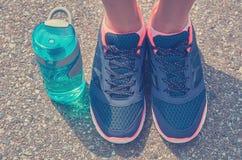 Les sports mettent en bouteille et les jambes dans des espadrilles se tiennent sur la route Images stock