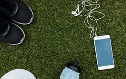 Les sports placent le garçon ou la fille, qui aiment courir Téléphone, écouteurs, chaussures, bouteille d'eau et puces pour le fo Images stock