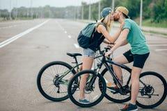 Les sports romantiques couplent des baisers sur le fond brouillé avec des bicyclettes Photos libres de droits
