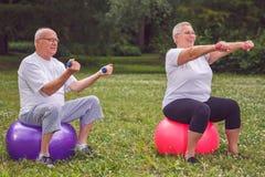 Les sports supérieurs couplent se reposer sur la boule de forme physique avec des haltères photographie stock libre de droits