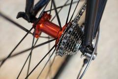 Les sports vont à vélo l'essieu arrière rouge avec emballer des vitesses de cassette sur les jantes légères photo stock