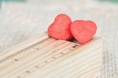Les sucreries de coeur ont enduit du sucre se reposant sur la règle Image stock
