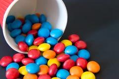 Les sucreries rondes multicolores de drag?e ont vers? d'une tasse de papier invers?e sur un fond noir images libres de droits