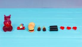 Les sucreries savoureuses représentent sous forme d'ours gommeux, hamburger et Images stock