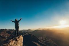 Les supports d'homme faisant face au Soleil Levant avec soulèvent ses bras sur le mont Sinaï photos stock