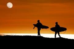 Les surfers marchant à l'océan pour un coucher du soleil conduisent images stock