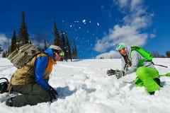 Les surfeurs couplent apprécient la station de sports d'hiver de la neige de précipitation Photographie stock