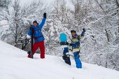 Les surfeurs heureux se tiennent dans la forêt après des chutes de neige Photo stock