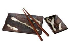 Les sushi bruns d'isolement ont placé avec des baguettes Photographie stock libre de droits
