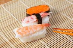 Les sushi délicieux du Japon se mélangent aux baguettes Photo libre de droits