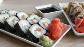 Les sushi de grand petit pain de la cuisine japonaise se trouvent sur une table dans un restaurant élégant, à côté d'un bol de sa banque de vidéos