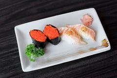 Les sushi de Maki avec des oeufs et des saumons de poissons de vol ont grillé des sushi de nigiri Photographie stock libre de droits